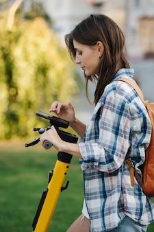 Brunette in het park check de instellingen voor het zijaanzicht van haar elektrische scooter