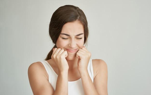 Brunette in wit t-shirt tanden problemen ontevredenheid grijs