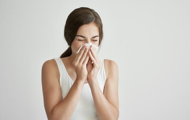 Brunette in wit t-shirt veegt haar gezicht af met een zakdoek gezondheidsproblemen koude. hoge kwaliteit foto