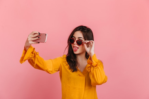 Brunette in zonnebril in vorm van hart toont haar tong, selfie maken op roze muur.