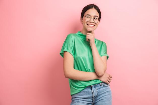 Brunette jong meisje met een ronde bril die haar kin aanraakt en aan de voorkant glimlacht, geïsoleerd over roze muur