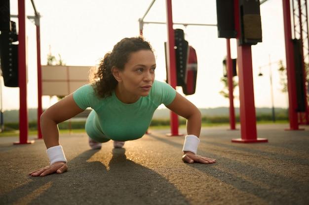Brunette jonge atletische gemengd ras vrouw doet push-ups in een sportveld in stedelijke omgeving. aantrekkelijke atletische sportvrouw die 's ochtends buiten traint, kopieer ruimte. gezondheid, fitnessconcept