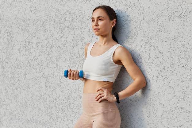 Brunette jonge volwassen vrouw met witte sportieve top en beige leggins die wegkijkt terwijl ze armen uitwerkt, oefeningen doet voor biceps en triceps, gezonde levensstijl.