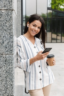 Brunette jonge vrouw in vrijetijdskleding die afhaalkoffie drinkt en mobiele telefoon vasthoudt terwijl ze boven het gebouw staat
