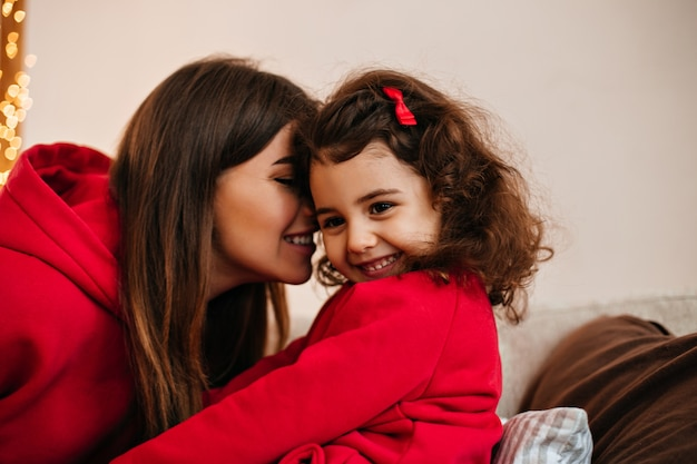 Brunette jonge vrouw kussen kind. binnen schot van moeder en klein kind thuis glimlachen.