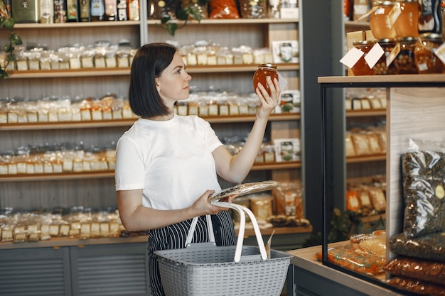 Brunette kiest eten. dame houdt een winkelwagentje. meisje in een wit overhemd in de supermarkt.