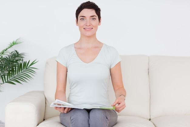 Brunette lachende vrouw met een tijdschrift