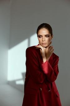 Brunette lichte make-up handen in de buurt van gezicht rode jas mode glamour lichte achtergrond