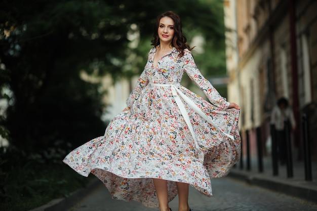 Brunette loopt door de straten van lviv in een mooie lange jurk