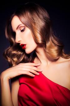 Brunette luxe vrouw in rode jurk met heldere huid en donkere avond make-up: groene kattenoog en bruine oogschaduw. golvend kapsel. donkere achtergrond