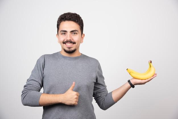 Brunette man banaan te houden en duimen opgevend.