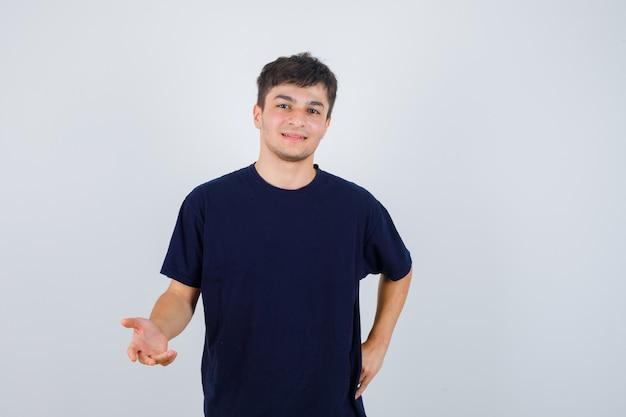 Brunette man die zich uitstrekt hand in vragend gebaar in t-shirt en op zoek vrolijk, vooraanzicht.