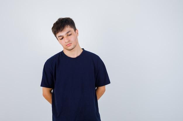 Brunette man hand in hand achter rug in t-shirt en peinzend, vooraanzicht op zoek.