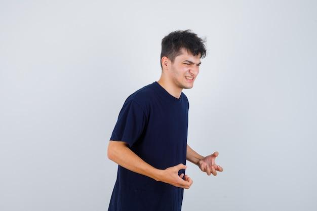 Brunette man houdt handen op agressieve manier in t-shirt en kijkt geïrriteerd. vooraanzicht.