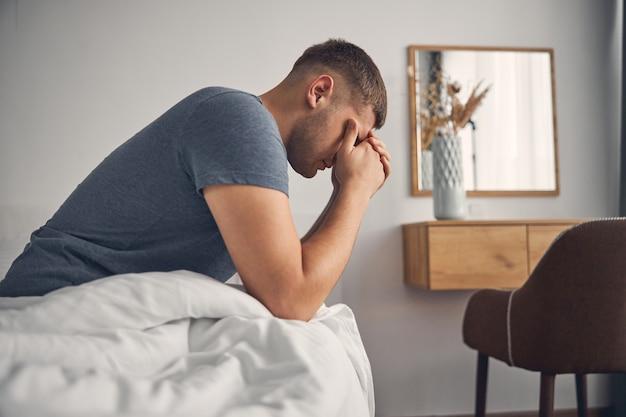 Brunette man in blauw t-shirt zittend op het bed in een gezellige sfeer terwijl hij zijn ogen met handen sluit