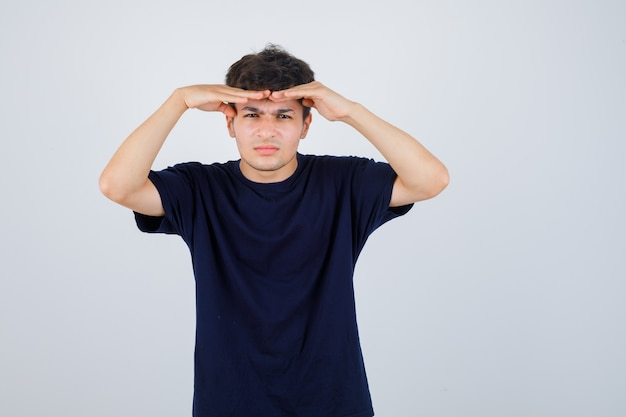 Brunette man in donkere t-shirt hand in hand om duidelijk te zien en peinzend, vooraanzicht op zoek.