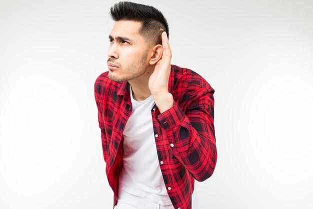 Brunette man in een geruit overhemd wijd open luistert af op een gesprek op een witte studio achtergrond.