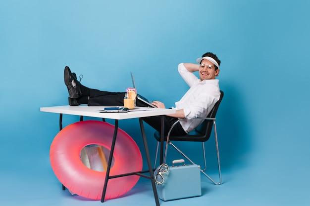Brunette man in pak werkt terwijl u ontspant met cocktail op blauwe ruimte met koffer en roze rubberen ring.