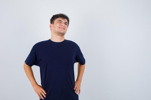 Brunette man in t-shirt hand in hand op de taille en op zoek naar pijnlijke, vooraanzicht.