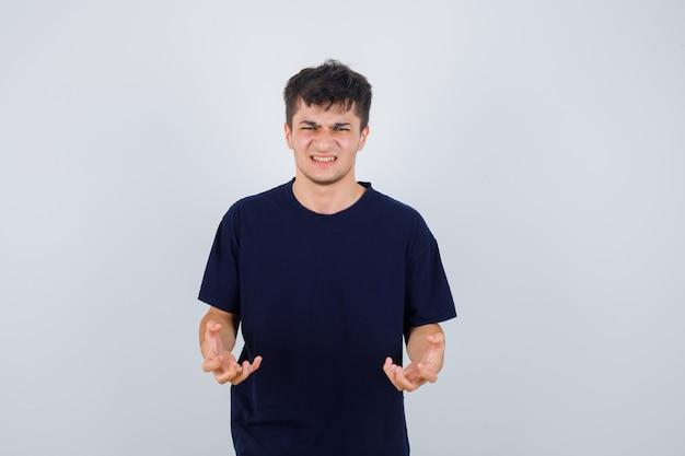 Brunette man in t-shirt handen houden op agressieve manier en op zoek geërgerd, vooraanzicht.