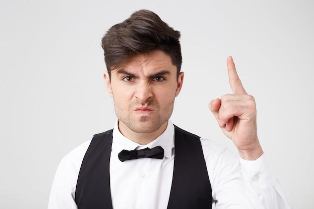 Brunette man in woede met opgestoken vinger probeert iemand zijn zaak te bewijzen, wil naar voren komen als leider uit een geschil