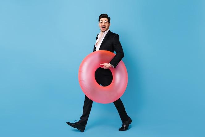 Brunette man in zwart klassiek pak glimlacht vreugdevol en beweegt met roze rubberen ring tegen blauwe ruimte.