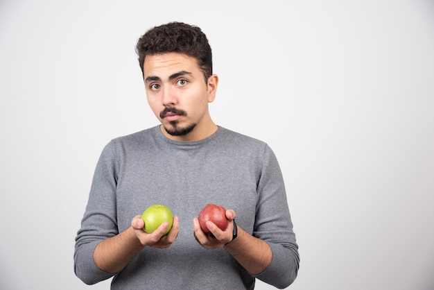 Brunette man met appels die zich voordeed op grijs.
