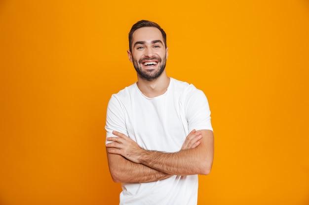 Brunette man met baard en snor lachend staand, geïsoleerd op geel