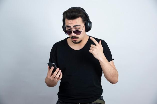 Brunette man model in zonnebril en koptelefoon met mobiele telefoon.