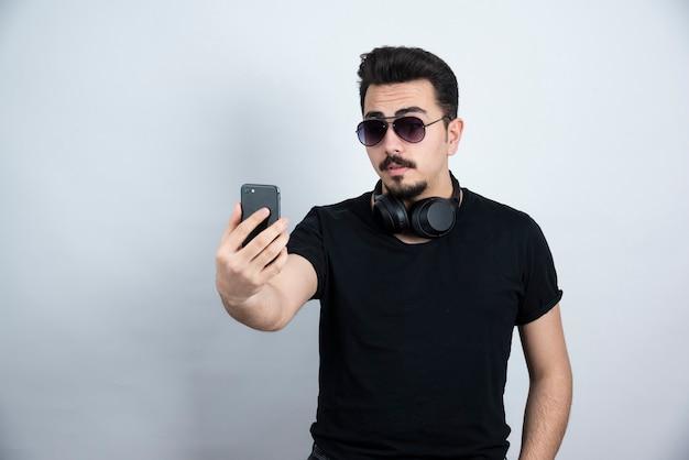 Brunette man model permanent in hoofdtelefoons en selfie te nemen.