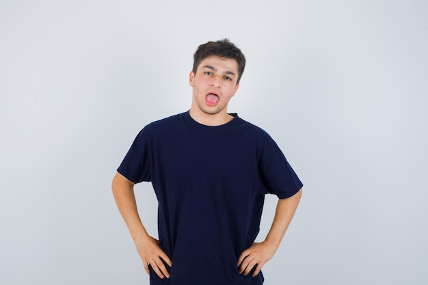 Brunette man mond openen, poseren met de handen op de taille in t-shirt en op zoek gericht, vooraanzicht.