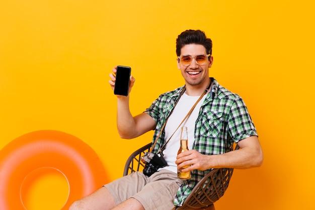 Brunette man toont zijn smartphone met een glimlach. man in shirt, t-shirt en korte broek zit op stoel met flesje bier op oranje ruimte met opblaasbare cirkel.