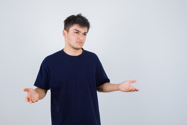 Brunette man vragen vraag gebaar maken in donkere t-shirt en op zoek teleurgesteld, vooraanzicht.