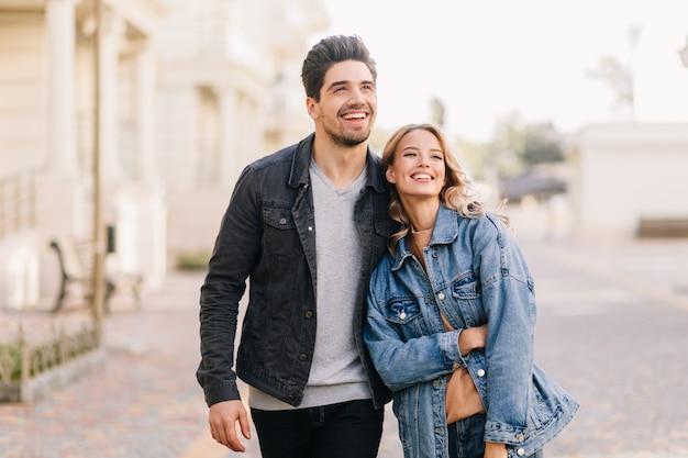 Brunette man wandelen met vriendin in weekend. openluchtportret van gelukkige jonge mensen die van datum genieten.