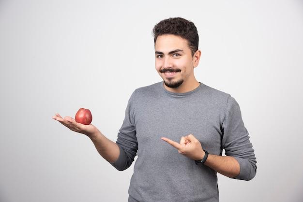 Brunette man wijzend op rode appel op grijs.