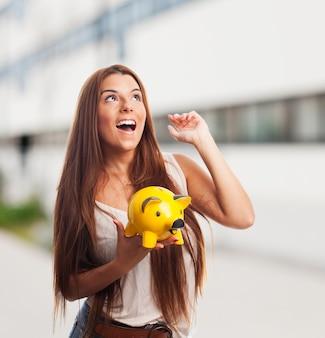 Brunette meisje bedrijf gele biggetje spaarpot