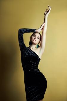 Brunette meisje gekleed in een chique zwarte avondjurk met een open schouder, mooie grote oorbellen in haar oren