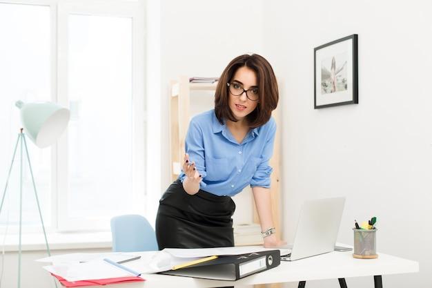 Brunette meisje in blauw shirt en zwarte rok staat in de buurt van tafel in kantoor. ze legde haar hand op de tafel. ze kijkt heel serieus naar de camera.