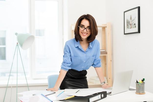 Brunette meisje in blauw shirt en zwarte rok staat in de buurt van tafel in kantoor. ze legde haar handen op de tafel. ze kijkt vriendelijk naar de camera.