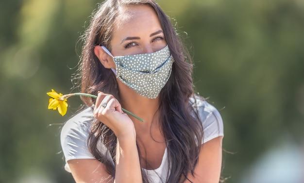 Brunette meisje in de natuur draagt een gezichtsmasker glimlachend, met een narcis in haar hand.