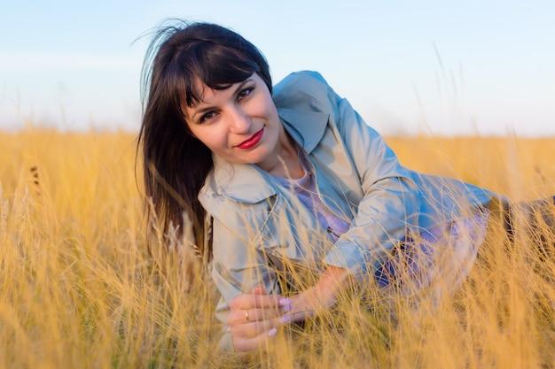 Brunette meisje in een blauwe jas ligt in een veld op geel gras.