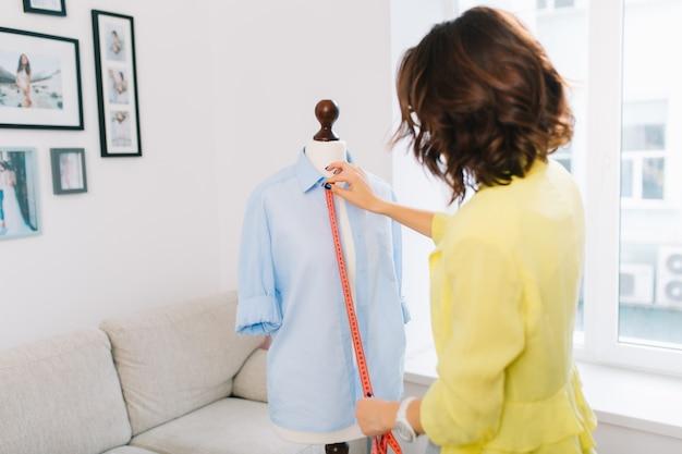 Brunette meisje in een gele jas maakt passend overhemd op etalagepop. ze werkt in een groot atelieratelier. de foto toont een uitzicht vanaf de achterkant.