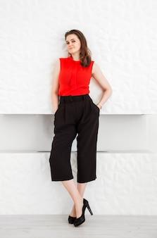 Brunette meisje in een rode blouse, zwarte capribroek en schoenen met hoge hakken poseren tegen de achtergrond van een witte open haard.