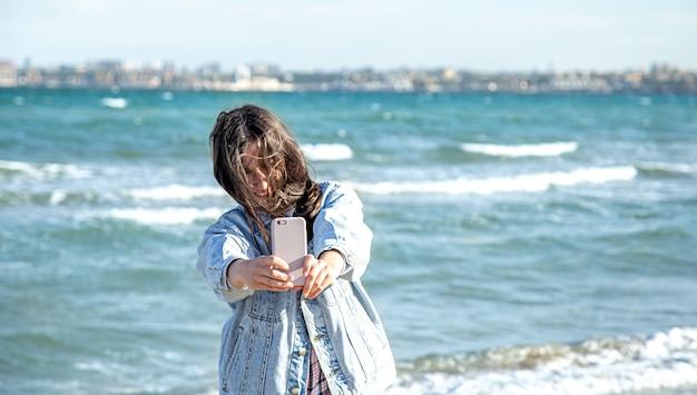 Brunette meisje in een spijkerjasje maakt een foto op een selfie cameratelefoon tegen de achtergrond van de zee. concept van reizen en nieuwe ervaringen.