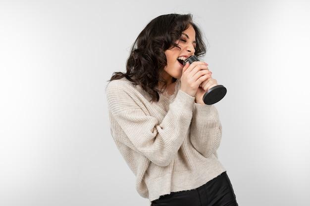 Brunette meisje in een witte trui houdt een retro microfoon in haar hand en zingt een lied op een witte achtergrond.