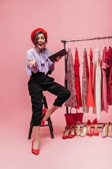 Brunette meisje in rode baret lacht zittend op een stoel met map in haar handen. dame met rode lippenstift poseren op roze achtergrond met standaard met glanzende jurken.