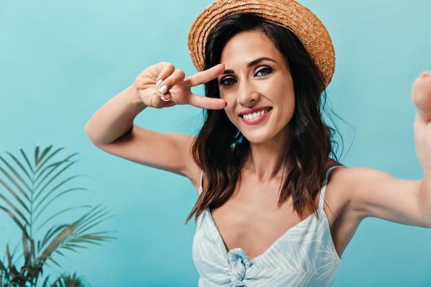 Brunette meisje in strooien hoed vertoont vredesteken en neemt selfie op blauwe achtergrond. mooie volwassen dame in lichte stijlvolle zomerjurk maakt foto.