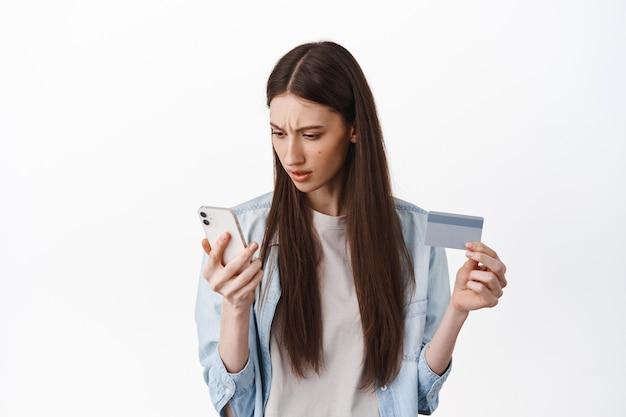Brunette meisje kijkt verward naar het scherm van de smartphone, houdt een creditcard vast, kan niet begrijpen hoe de kaart moet worden geregistreerd om een bestelling te plaatsen, staande over een witte muur