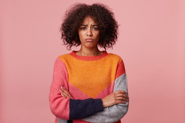 Brunette meisje met afro kapsel beledigd verdrietig boos, pruilde haar lippen, is overweldigd door negatieve emoties, in slecht humeur, staan met gekruiste armen, kleurrijke trui dragen, geïsoleerd op roze