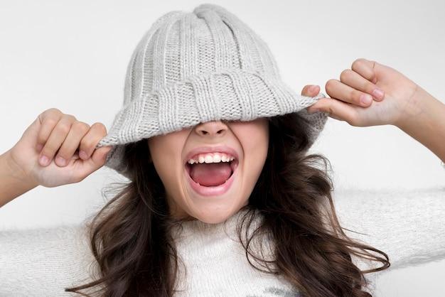 Brunette meisje met de hoed op haar ogen schreeuwen